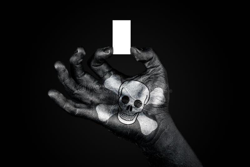 Main avec les pirates peints d'un drapeau tenant une petite feuille blanche avec l'espace pour une inscription, faux  image stock