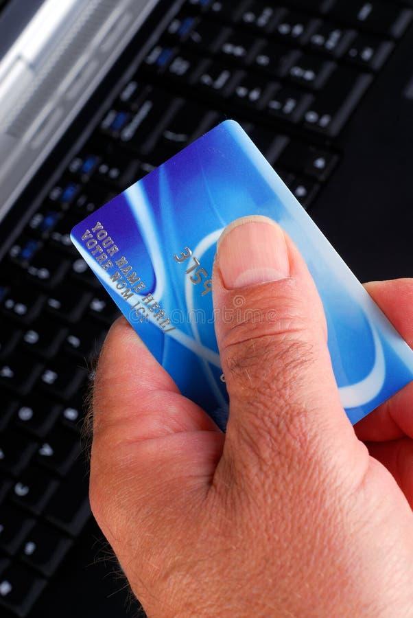 Main avec par la carte de crédit image stock