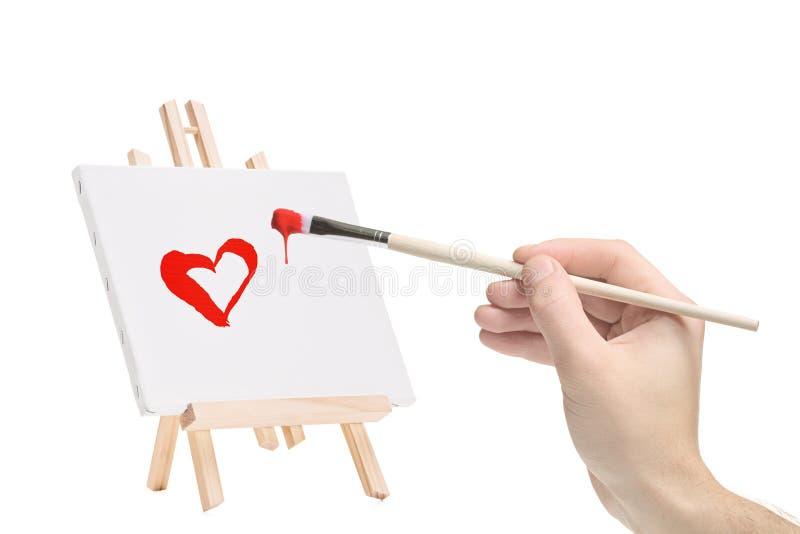 Main avec un pinceau et une peinture d'un coeur photo stock