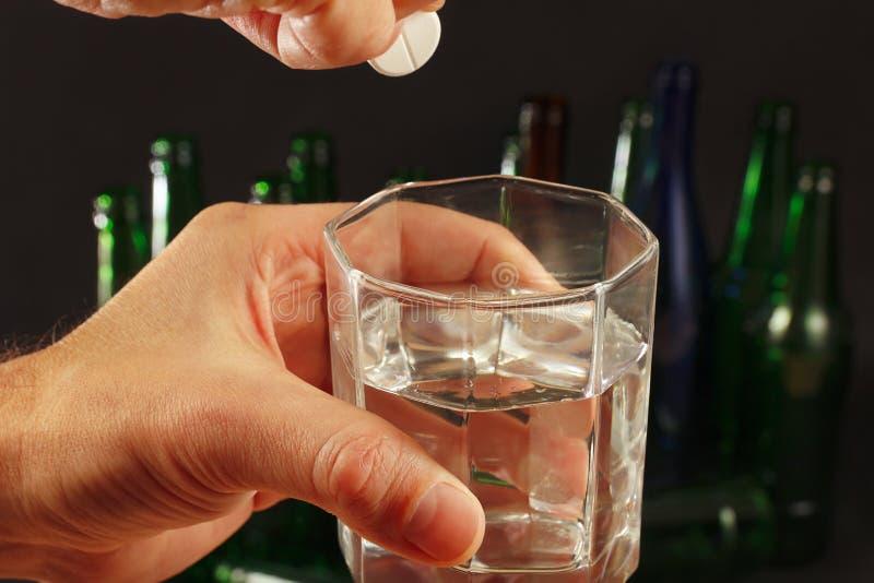 Main avec une pilule effervescente de gueule de bois au-dessus de verre de l'eau sur un fond foncé photographie stock