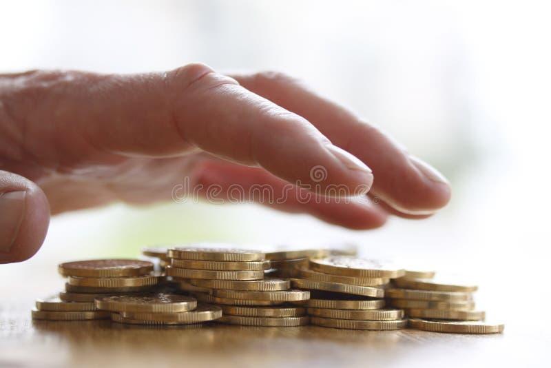 Main avide saisissant ou atteignant pour la pile des pièces de monnaie d'or De fin concept - pour l'impôt, la fraude et l'avidité photographie stock