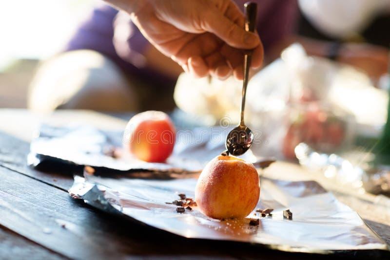 Main bourrant le chocolat Chips Into Apple photographie stock libre de droits