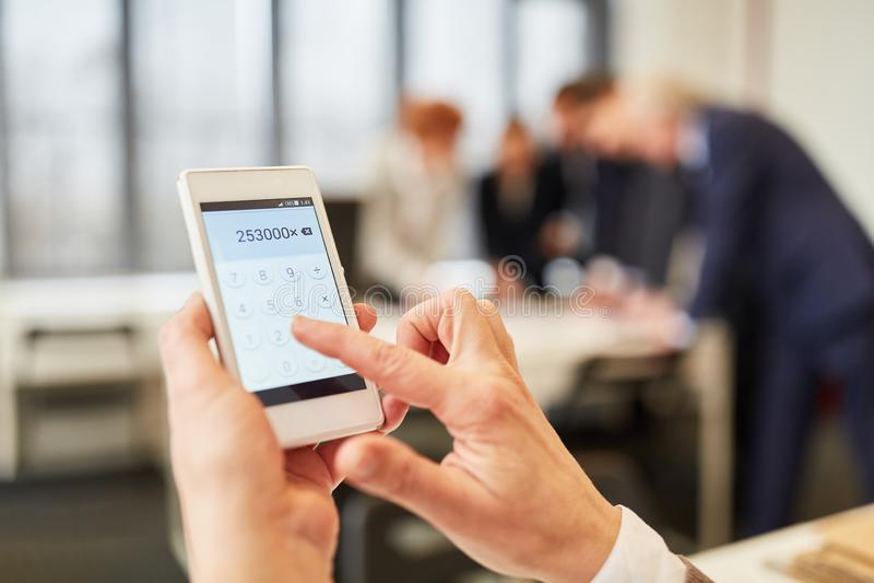 Main calculant avec la calculatrice d'appli de smartphone images stock