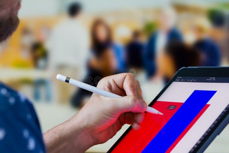 Main caucasienne cultivée de fin utilisant un iPad pour faire la conception graphique sur un APP photo libre de droits
