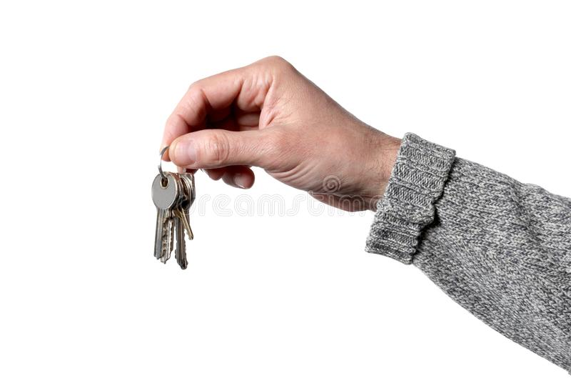 Main caucasienne du ` s d'homme jugeant des clés d'isolement sur le fond blanc avec le chemin de coupure photos libres de droits