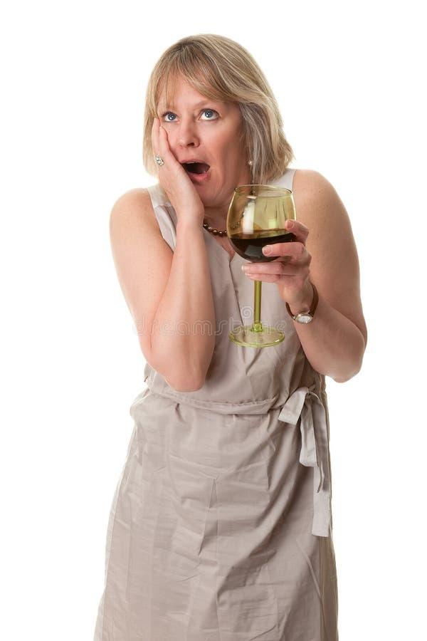Main choquée de femme au visage avec du vin photographie stock libre de droits