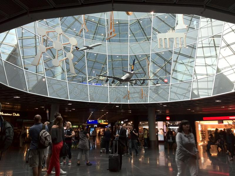 The main commercial and meeting area in Frankfurt airport. Under this huge naturally lighted glass atrium with hanging symbols of landmarks of European cities stock photo