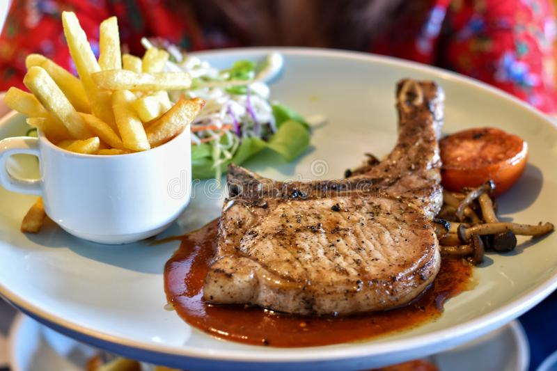 Main course pork t-bone steak with vegetables salad in white dish. royalty free stock images