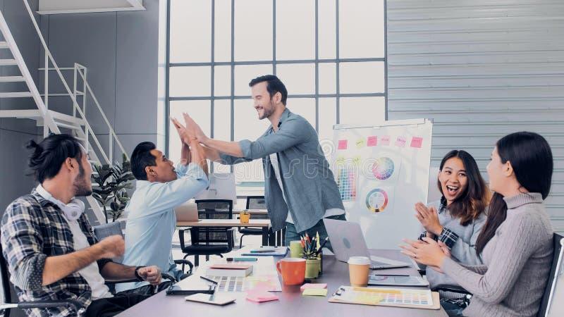 Main créative d'applaudissements d'avance d'équipe de directeur avec l'équipe de concepteur à la table de réunion idée de discuss photos stock