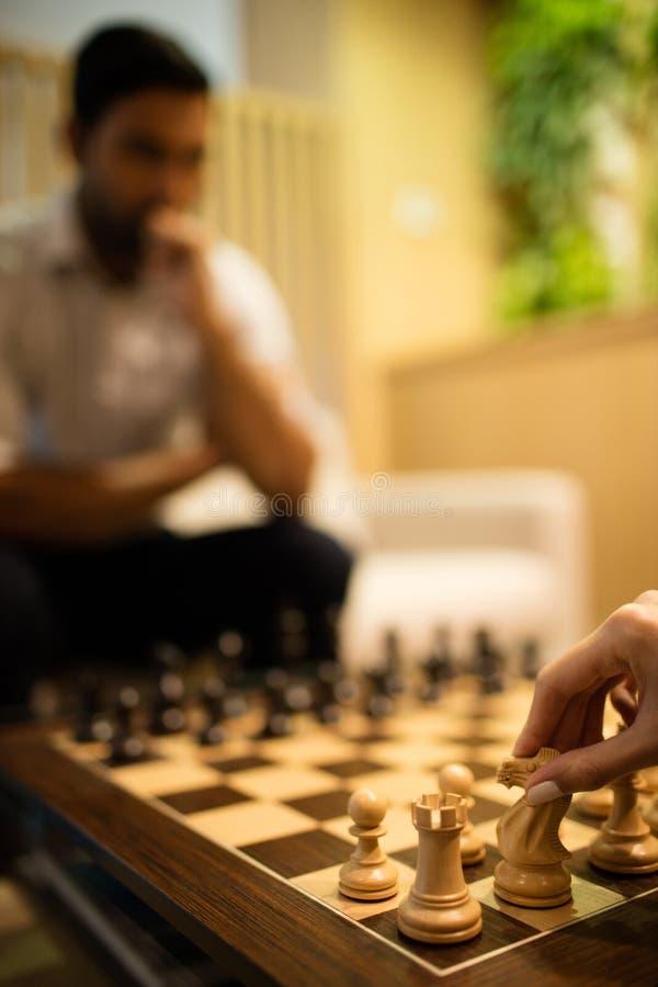 Main cultivée de femme d'affaires jouant des échecs avec le collègue masculin photographie stock libre de droits