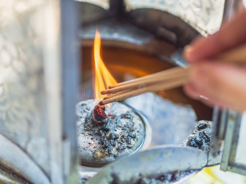 Main cultivée de femme lighning l'encens du feu de lanterne pour la prière photographie stock