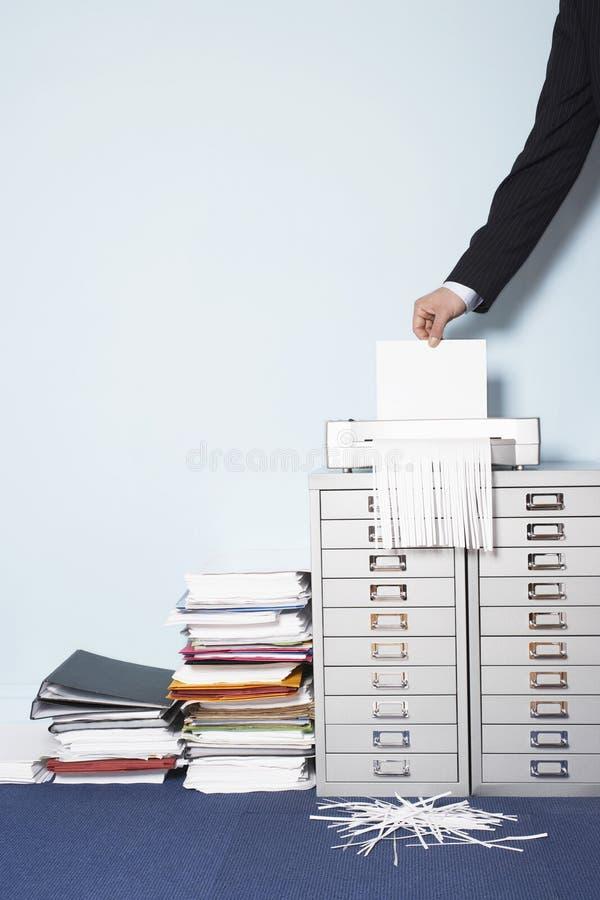 Main déchiquetant le document dans le bureau photo libre de droits