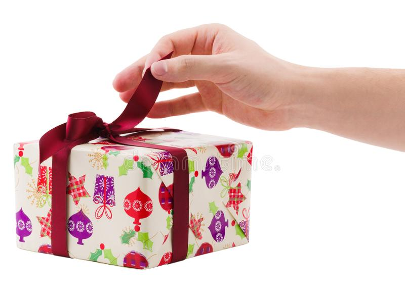 Main déliant un ruban d'un boîte-cadeau D'isolement sur le fond blanc photo stock