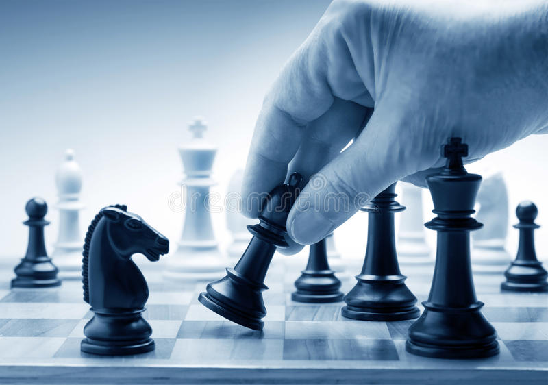 Main déplaçant une pièce d'échecs à bord image stock