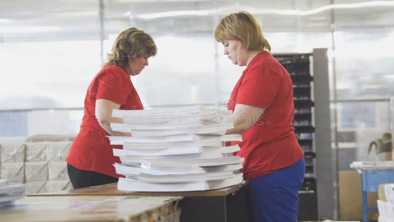 Main-d'œuvre féminine assortissant des piles de papier dans la typographie photos libres de droits