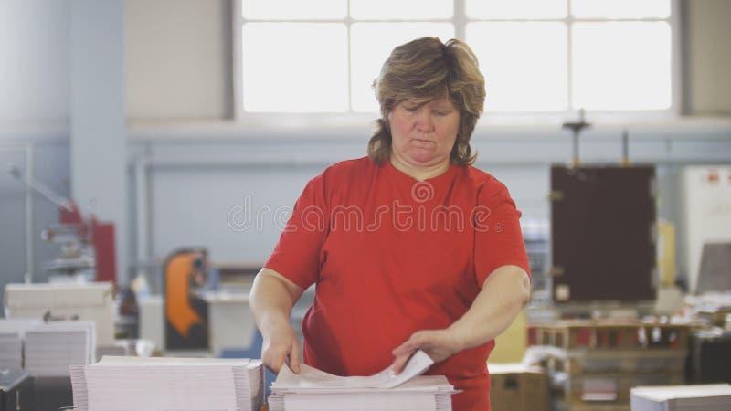 Main-d'œuvre féminine assortissant des piles de papier dans la typographie images libres de droits