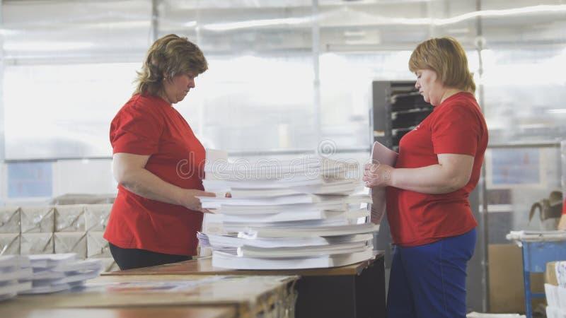 Main-d'œuvre féminine assortissant des piles de papier dans la typographie image stock