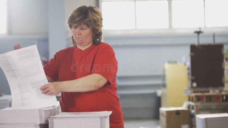Main-d'œuvre féminine assortissant des piles de papier dans la typographie images stock