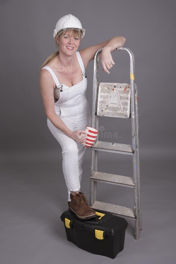 Main-d'œuvre féminine avec le pied sur sa boîte à outils photo libre de droits