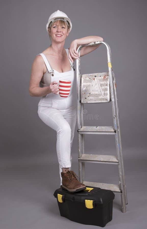 Main-d'œuvre féminine avec le pied sur sa boîte à outils photographie stock