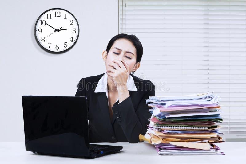 Main-d'œuvre féminine baîllant dans le bureau photos stock