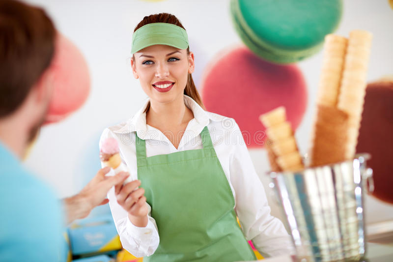 Main-d'œuvre féminine en confiserie donnant la crème glacée au client photos stock