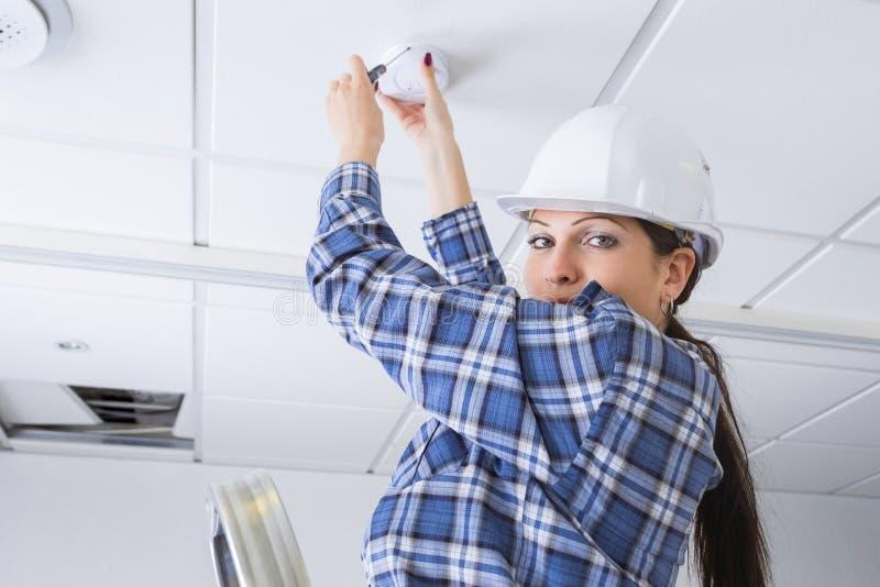 Main-d'œuvre féminine installant le détecteur de fumée à la maison image stock