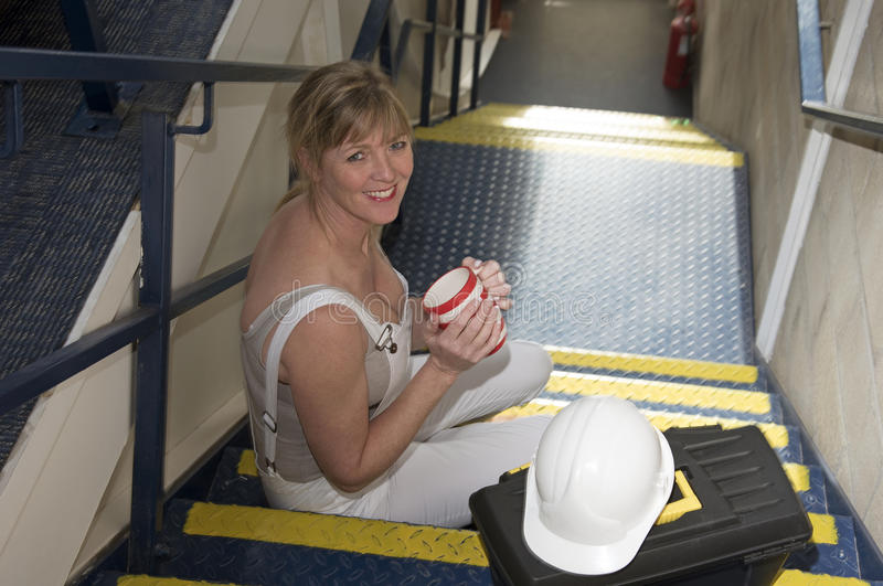 Main-d'œuvre féminine prenant une pause café se reposant avec une boîte à outils image libre de droits