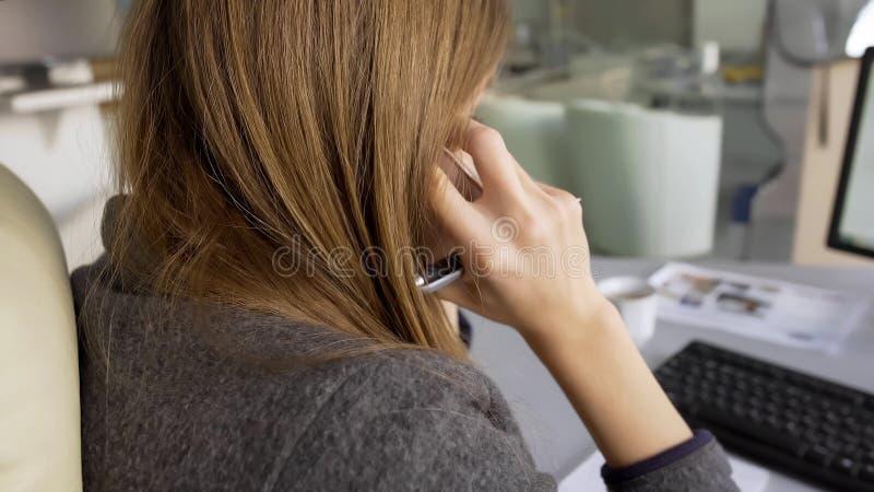 Main-d'œuvre féminine s'asseyant dans son fauteuil confortable et parlant au téléphone avec des investisseurs photo stock