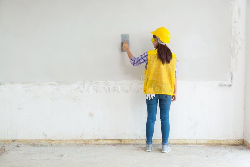 Main-d'œuvre féminine, travail plâtrant le mur en béton blanc à la maison, Hou photo libre de droits