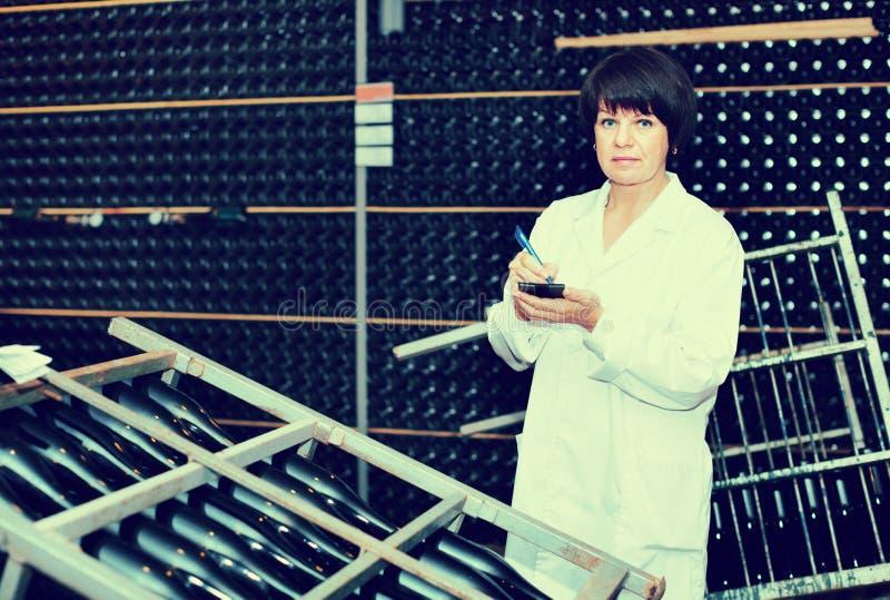 Main-d'œuvre féminine vérifiant la fermentation secondaire photos stock