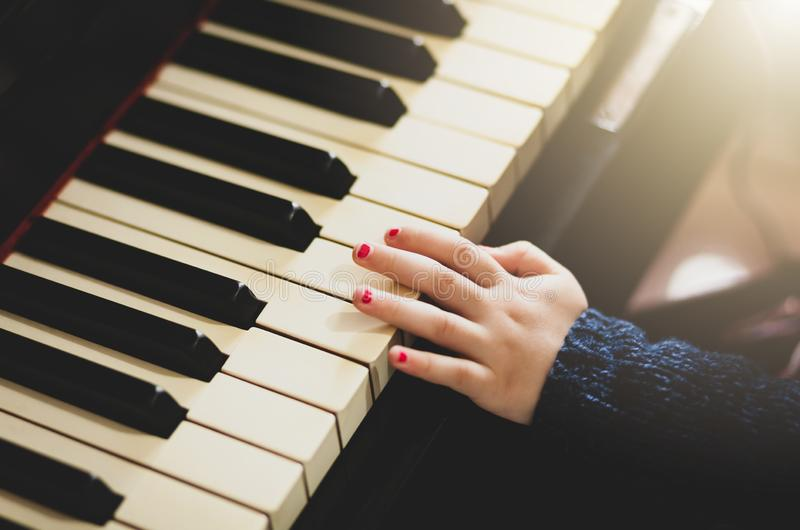 Main d'enfant en bas âge de fille jouant le piano photos libres de droits
