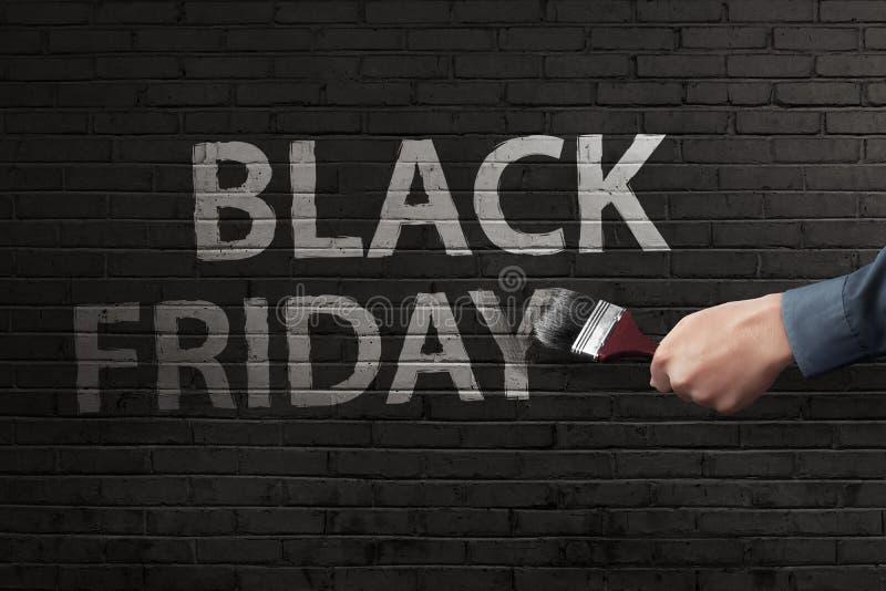 Main d'homme écrivant le texte blanc de Black Friday photographie stock libre de droits