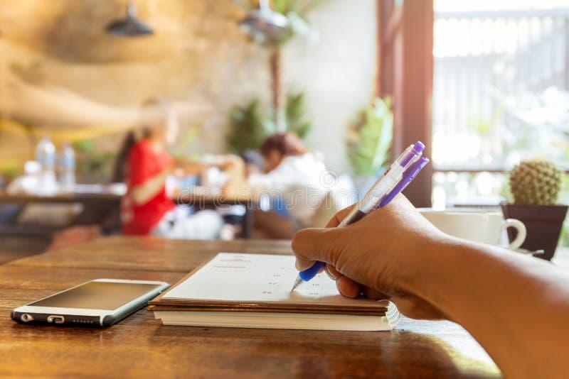 Main d'homme d'affaires écrivant le programme en journal intime de calendrier avec le stylo sur la table photos libres de droits