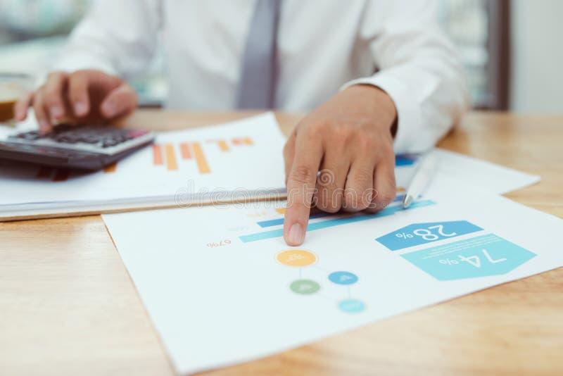 main d'homme d'affaires fonctionnant avec des finances au sujet de coût et de calculatrice photos stock