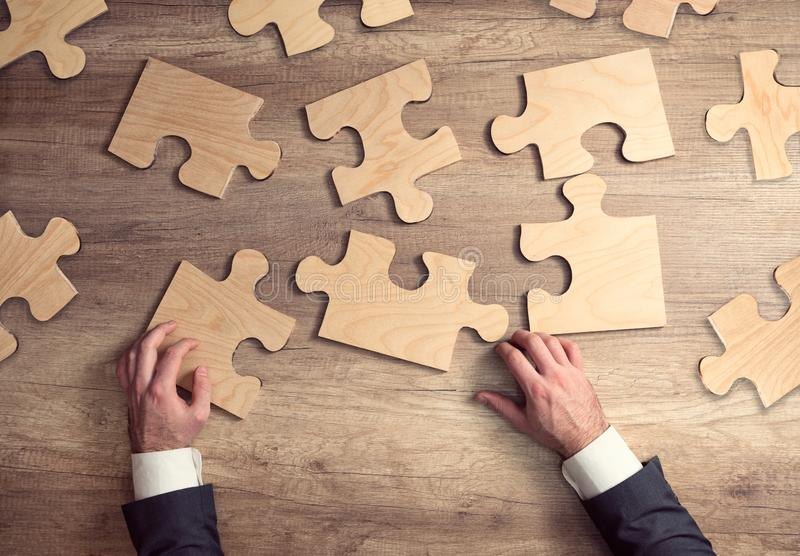 Main d'homme d'affaires reliant le puzzle denteux photos stock