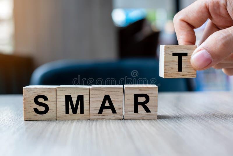 Main d'homme d'affaires tenant le bloc en bois de cube avec le mot FUTÉ d'affaires sur le fond de table Spécifique, réalisable, m images libres de droits