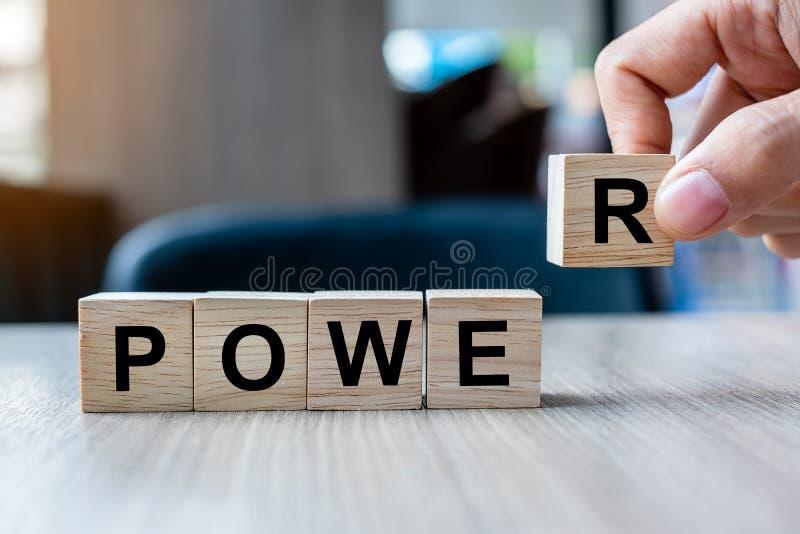 Main d'homme d'affaires tenant le bloc en bois de cube avec le mot d'affaires de PUISSANCE sur le fond de table Les mots ont le c image libre de droits