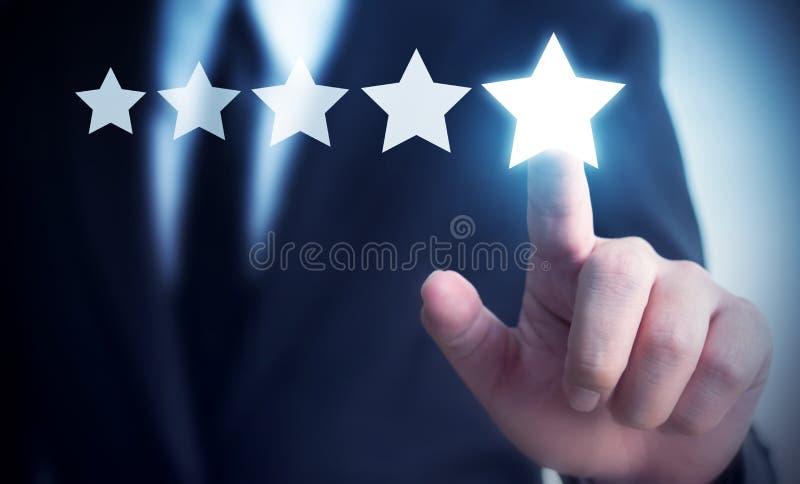 Main d'homme d'affaires touchant le symbole de cinq étoiles photo libre de droits