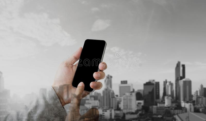 Main d'homme d'affaires utilisant le téléphone intelligent mobile avec le fond moderne de ville de double exposition, écran noir  image libre de droits