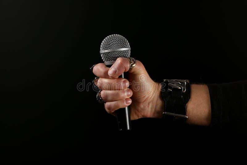 Main d'homme avec le microphone d'isolement sur le noir photos libres de droits