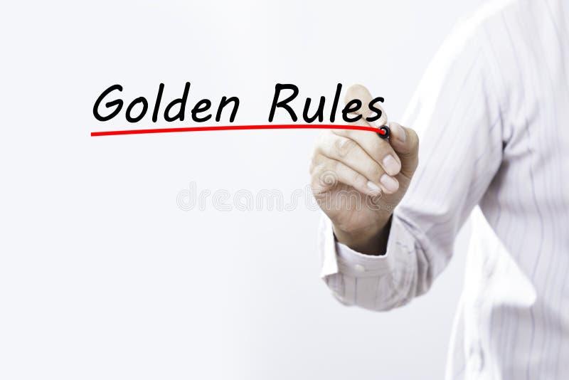 Main d'homme d'affaires écrivant des règles d'or avec le marqueur rouge sur le transpa photos libres de droits