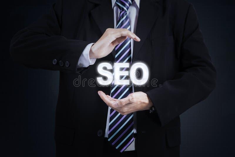 Main d'homme d'affaires avec le mot de SEO photos libres de droits