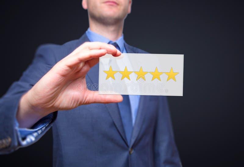 Main d'homme d'affaires jugeant cinq étoiles d'isolement sur le fond noir photo stock