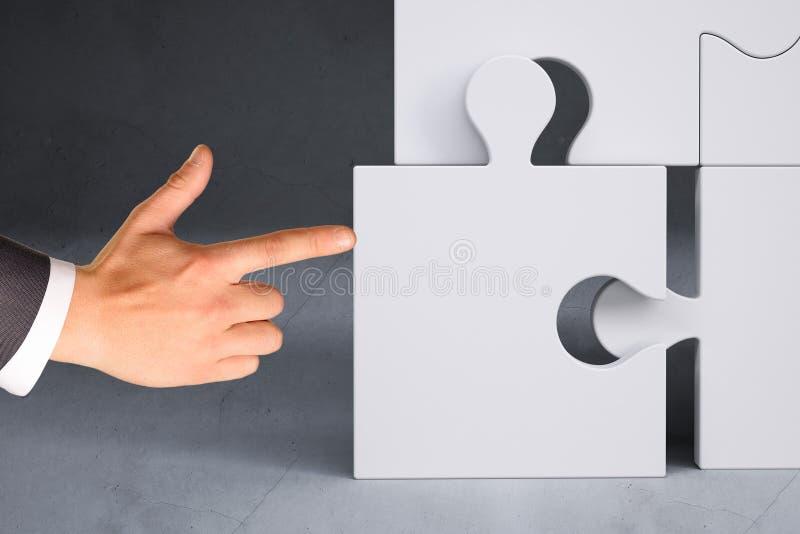 Main d'homme d'affaires poussant le morceau de puzzle photographie stock