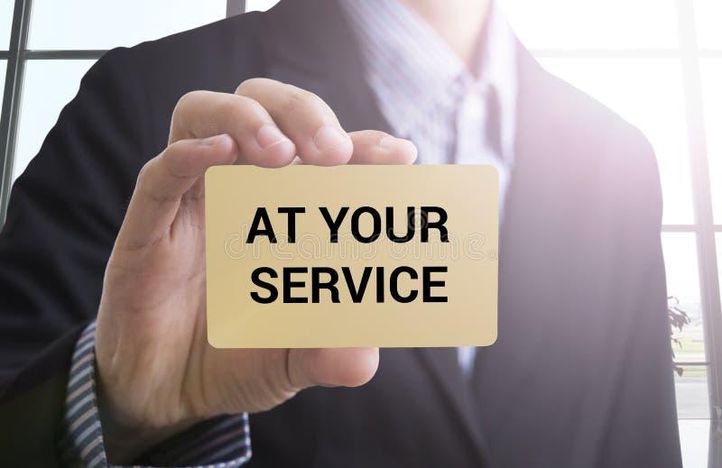 Main d'homme d'affaires tenant la carte de visite professionnelle de visite avec le message à votre service photographie stock libre de droits