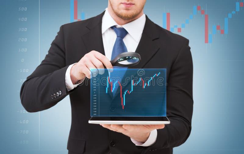 Main d'homme d'affaires tenant la loupe au-dessus du PC de comprimé images stock