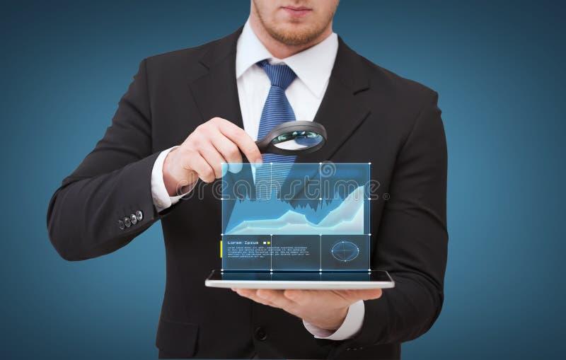 Main d'homme d'affaires tenant la loupe au-dessus du PC de comprimé photos libres de droits