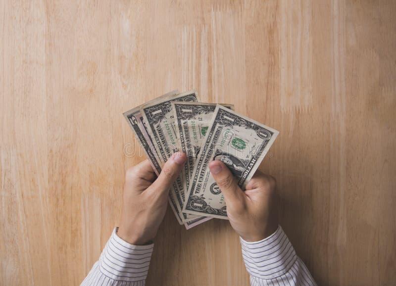 Main d'homme d'affaires tenant le dollar sur la table en bois dans le bureau image stock