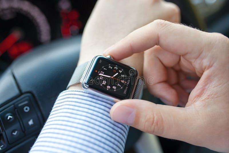 Main d'homme dans la voiture avec la montre et l'horloge d'Apple photos stock